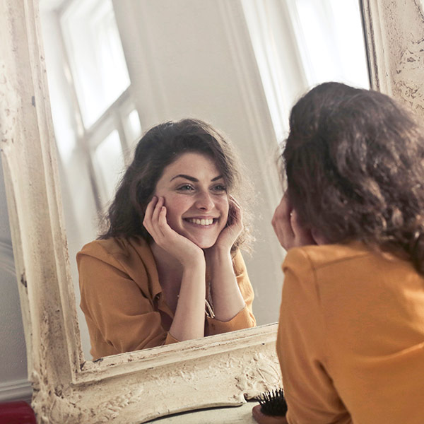 Smiling Woman Looking In A Mirror