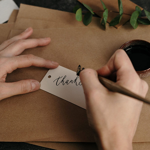 Person Writing A Thank You Note With A Quill And Ink