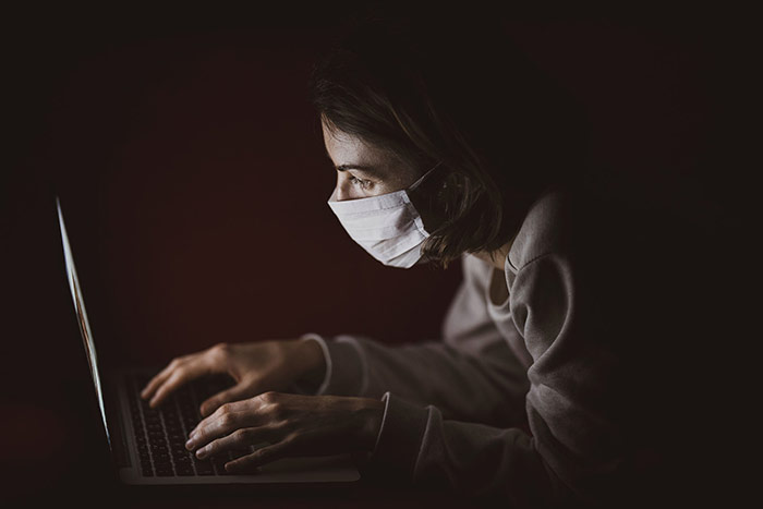 Woman Wearing A Mask Using A Laptop In The Dark