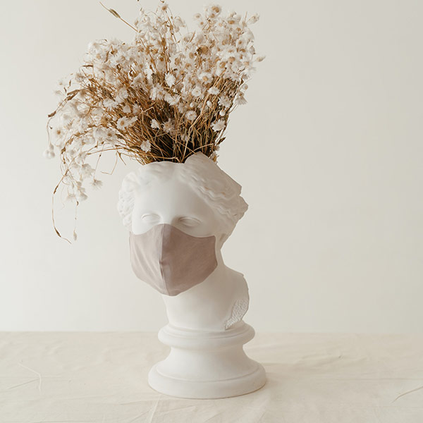 White Bust Of A Woman Wearing A Mask That Doubles As A Vase